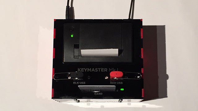 A photograph of the Keymaster machine from above. The machine has two USB ports on top labeled 'Red USB' and 'Black USB', along with a credit card sized slot labeled 'Card'.